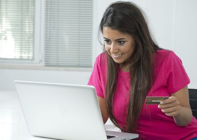 Smiling young woman shopping online with credit card and laptop computer.