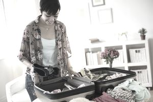 Mixed race woman packing suitcase for vacation
