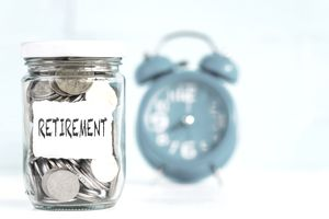 Glass jar coins with alarm clock background for retirement concept.