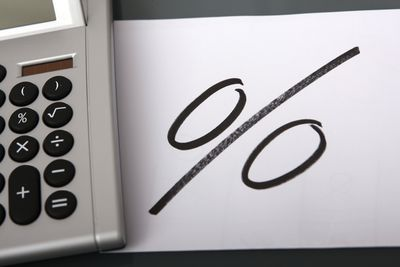 A calculator next to piece of paper with a scribble percent sign