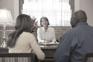 Couple meets with a businesswoman in her office