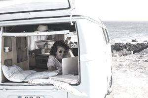Woman laying with her computer in her van