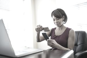 Businesswoman swiping credit card using reader