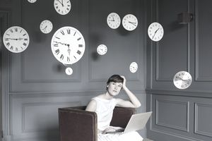 Woman on laptop, surrounded by clocks, wondering when her credit card payment is due
