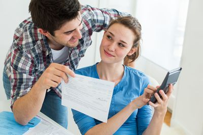Couple calculating and looking over open enrollment paperwork