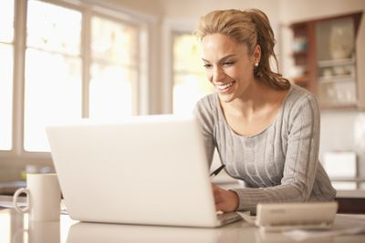 Woman in kitchen smiles while typing on a laptop