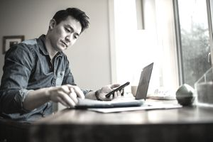 Man in home office on phone figuring out finances