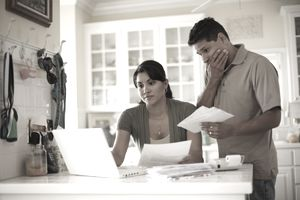 A worried couple looks at their credit report on a laptop surrounded by paperwork while holding bills in their hands