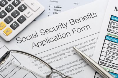 Social security benefits application form with a pen, glasses, calculator and documents.