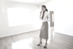Smiling female realtor talking on a cellphone in empty house