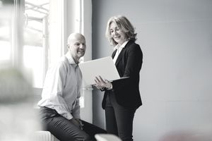 A female executive showing her male colleague information on a laptop