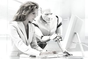 woman at computer next to a robot