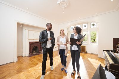 Couple looking at a vacant property with a real estate agent