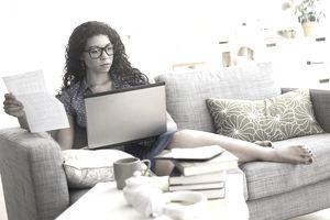 Woman paying bills on laptop on sofa