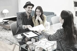 Young man and woman signing and handing documents to a woman at a glass desk.