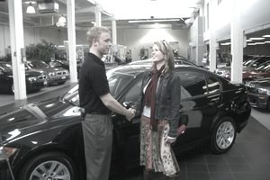 Woman shaking hands with a car salesman inside a dealership after financing a new car.