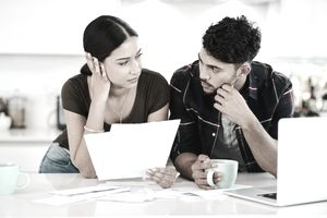 A young couple look at one another, stressed out, as they hold papers while drinking coffee in their kitchen and deciding whether to file a home insurance claim.