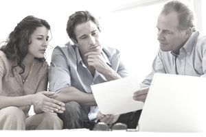Couple reviewing documents with a businessman