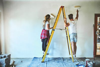 A couple painting the walls of their new home