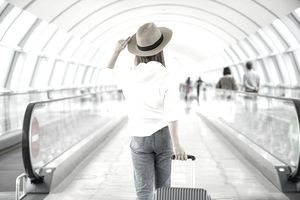 An airline passenger makes her way through the airport terminal.