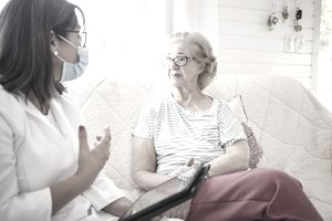 Female home caregiver visiting a senior woman with alzheimer disease at home.