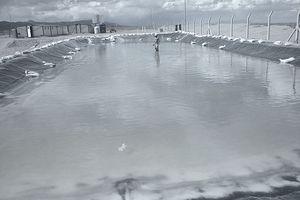 Worker walking ankle deep in fluid in a lithium brine pond at Lithium America in Argentina.