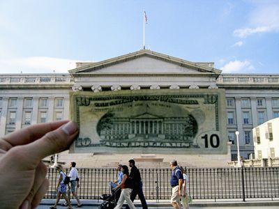Hand holding up a $10 bill in front of the U.S. Treasury
