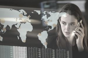 Businesswoman on cell phone looking at global map