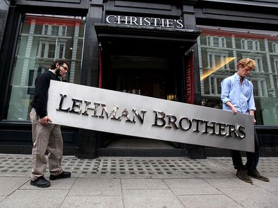 Two male employees of Christie's auction house maneuver the Lehman Brothers corporate logo in preparation for the liquidation of the firm's assets.