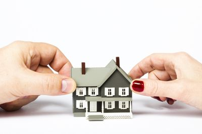 male and female hands holding on to a tiny model house