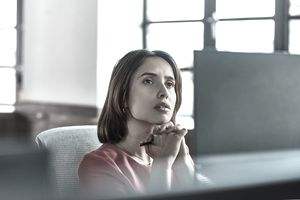 A business woman sits behind a computer screen, hands clasped and stares, deep in thought.