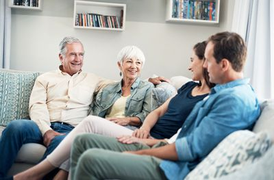 Senior parents sitting with adult couple