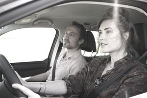 Woman driving while sitting beside man in car