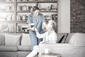 Older woman experiencing the benefits of long-term care insurance with a home health care aide