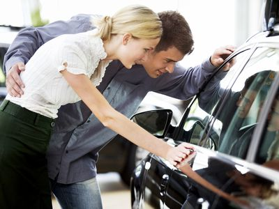 young couple looking at the window sticker of a new car