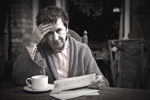An elderly woman in a robe contemplates a medical debt bill over a cup of coffee.