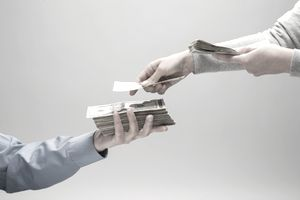 Close-up of man's hands counting a stack of money into another man's hand