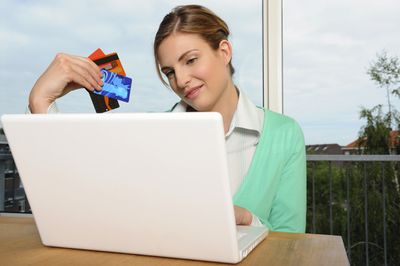 Woman holding credit cards while shopping online