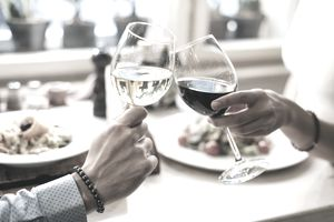 Two people at a table toasting with glasses of wine representing wine investing.