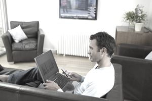 In a living room with the television display on, a man sits with a laptop in his lap while holding a tv remote