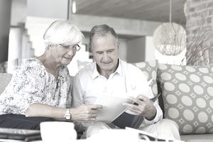Older couple reading papers together on sofa