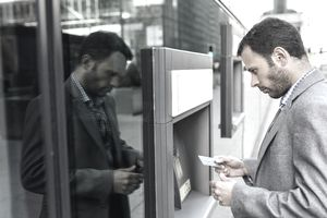 Businessman taking money at an ATM in the city.