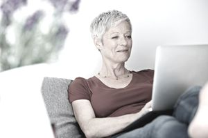 Woman lounging on a sofa with a laptop planning a retirement budget