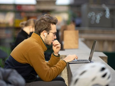 Man wearing spectacles working on a laptop