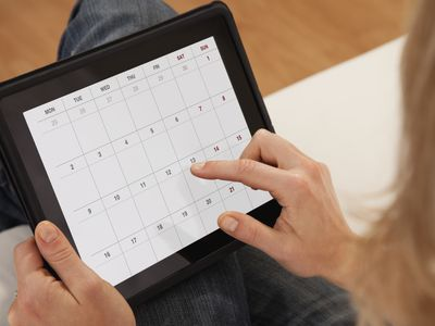 A woman is selecting a date on her tablet