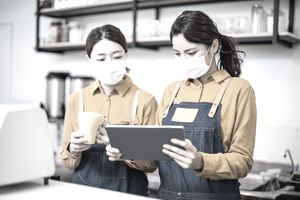 Asian young women clerks wearing face masks use a tablet to check the order for guests.