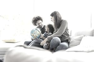 Mother, father, and child sitting on a couch together, holding a globe