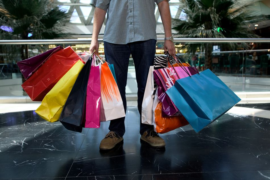 Man holding shopping bags in mall, low section