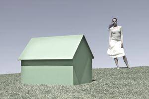 woman looking at small green house, representing Pax World Mutual Funds