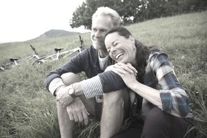 Laughing retired couple sitting in grass near two bicycles.